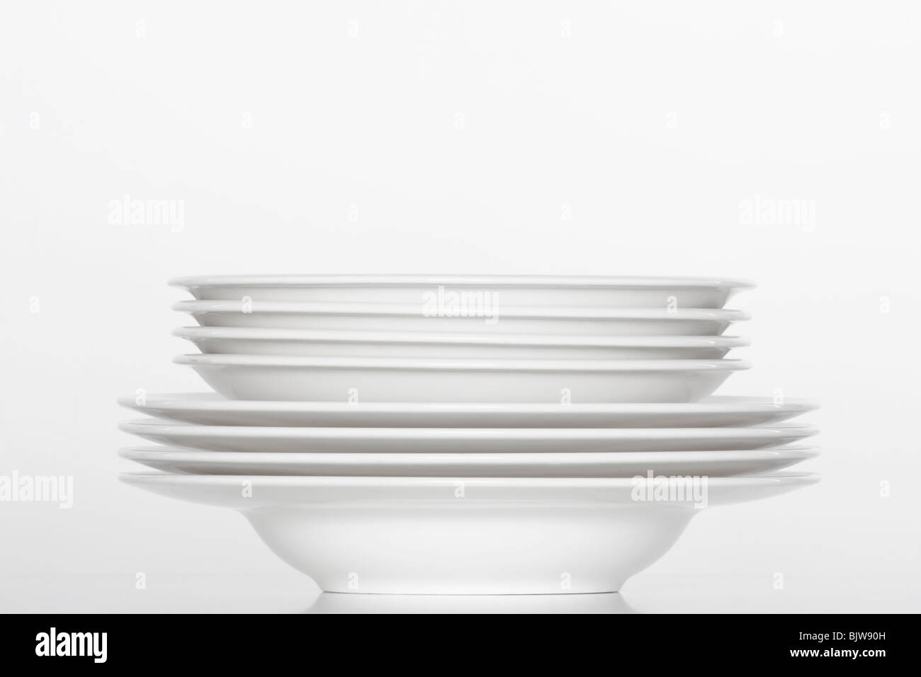 studio shot of a pile of white plates isolated on white - Stock Image