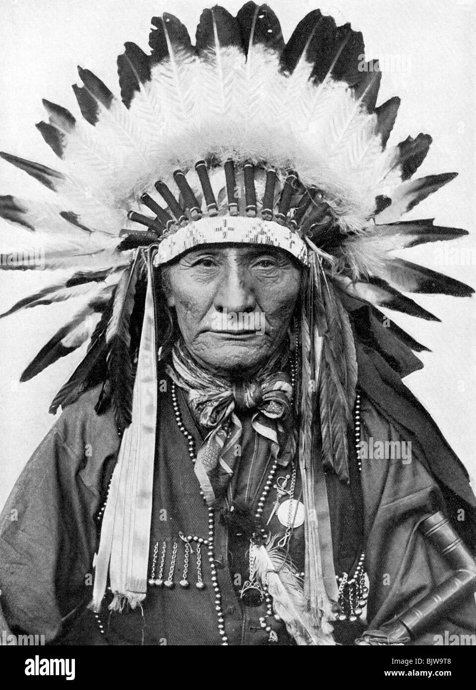 A Native American chief wearing his headdress. - Stock Image