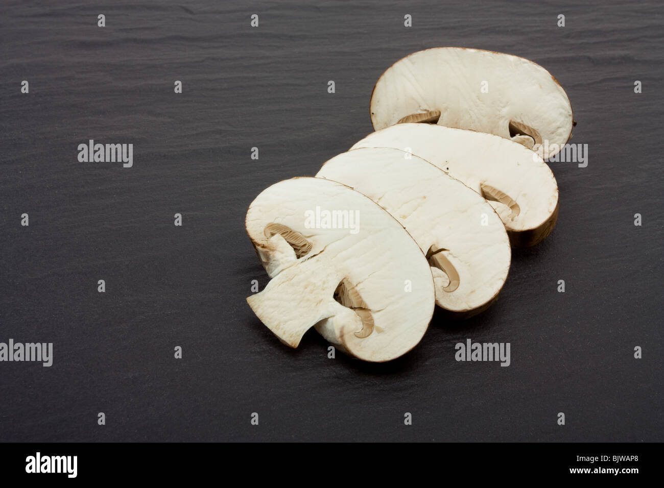 Sliced and whole Chestnut Mushrooms on background of dark slate. - Stock Image