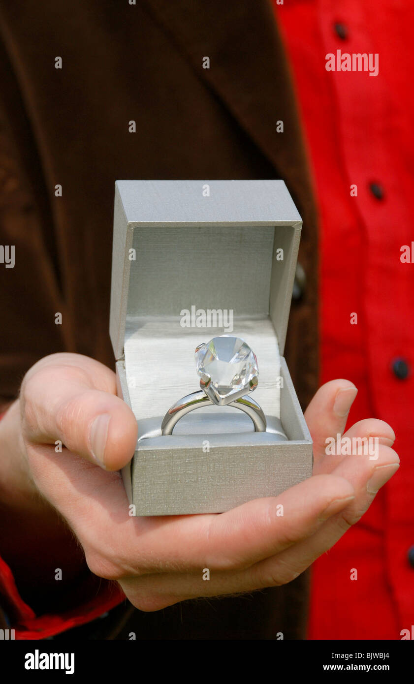 Man holding a box with an oversized diamond engagement ring inside. - Stock Image