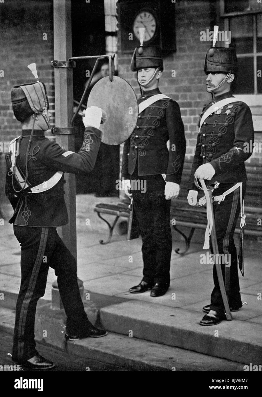 Striking the gong at the main gate of the Aldershot cavalry barracks, Hampshire, 1896. Stock Photo