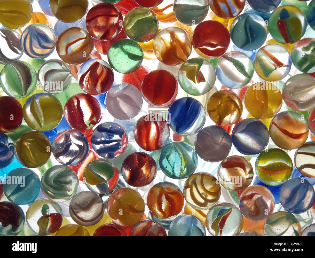 Colorful marbles in a glass bowl on top of a light table. - Stock Image