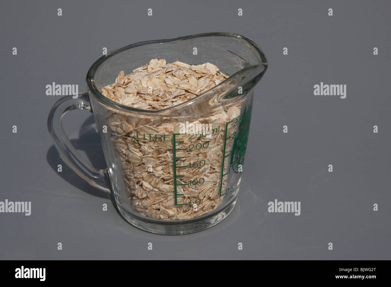 Dry Oatmeal in measuring cup - Stock Image