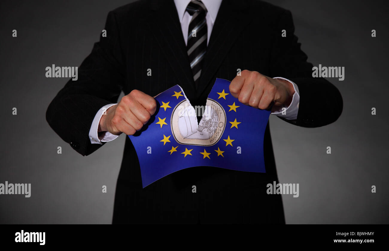 Man in a suit tearing apart the emblem of the European Union with the Euro in the centre - Stock Image