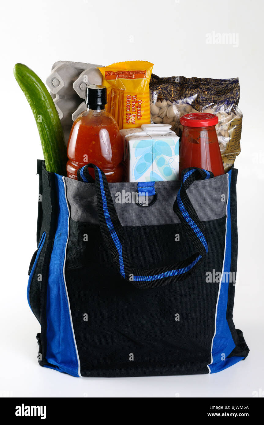 Reusable grocery bag filled with food from grocery store shopping trip - Stock Image