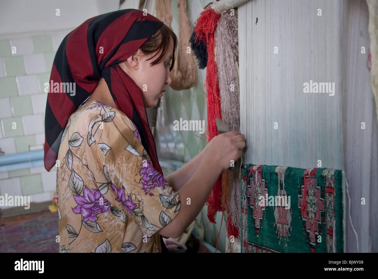 Young woman weaving a silk carpet in a Carpet Factory in Uzbekistan. - Stock Image