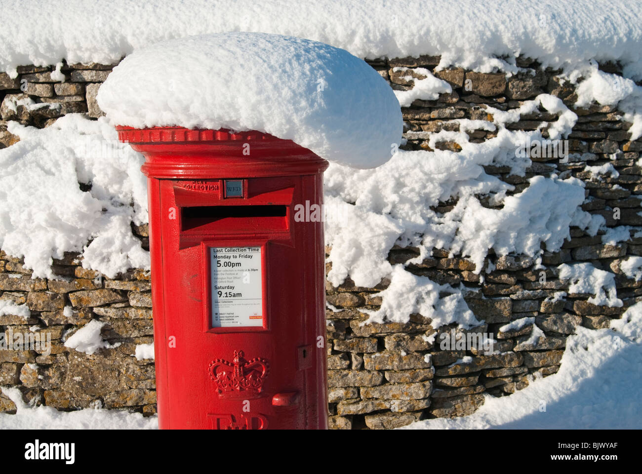 Red postbox in the snow Tackley Oxfordshire England UK - Stock Image