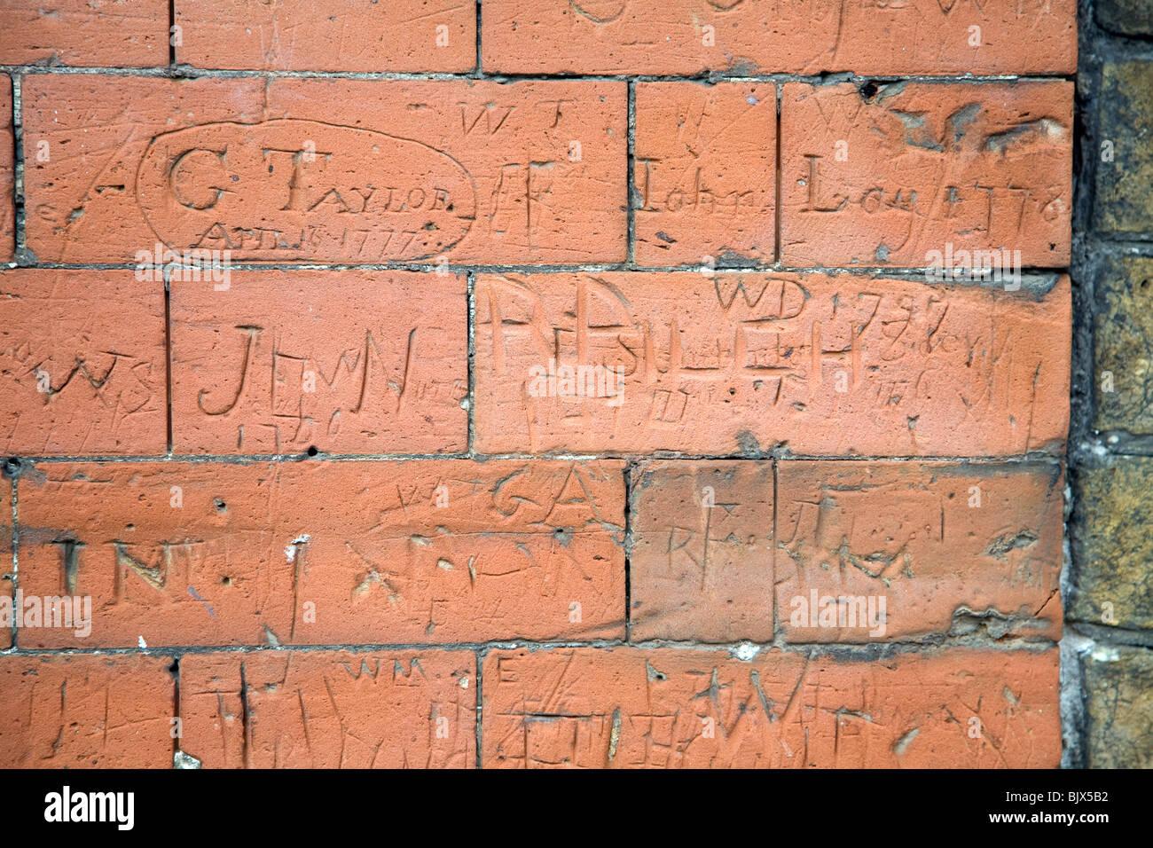 Eighteenth century graffiti scratched on brick wall of school building, Dedham, Essex - Stock Image
