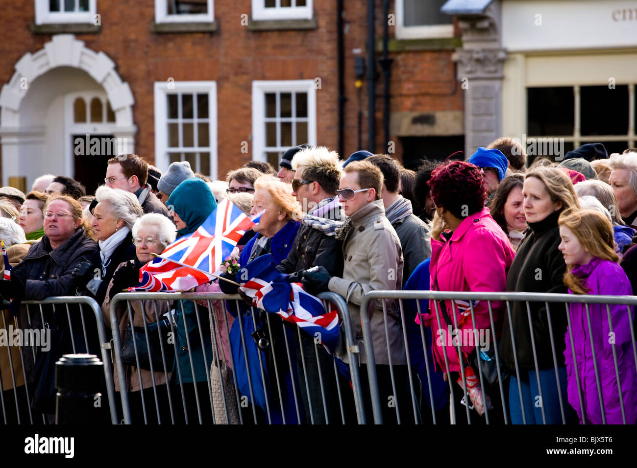 Eager crowds of onlookers wait to see The Queen attend Maundy Thursday Easter celebrations outside Derby Cathedral. - Stock Image