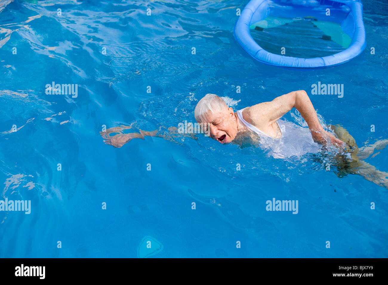 Elderly man swimming in a pool. - Stock Image