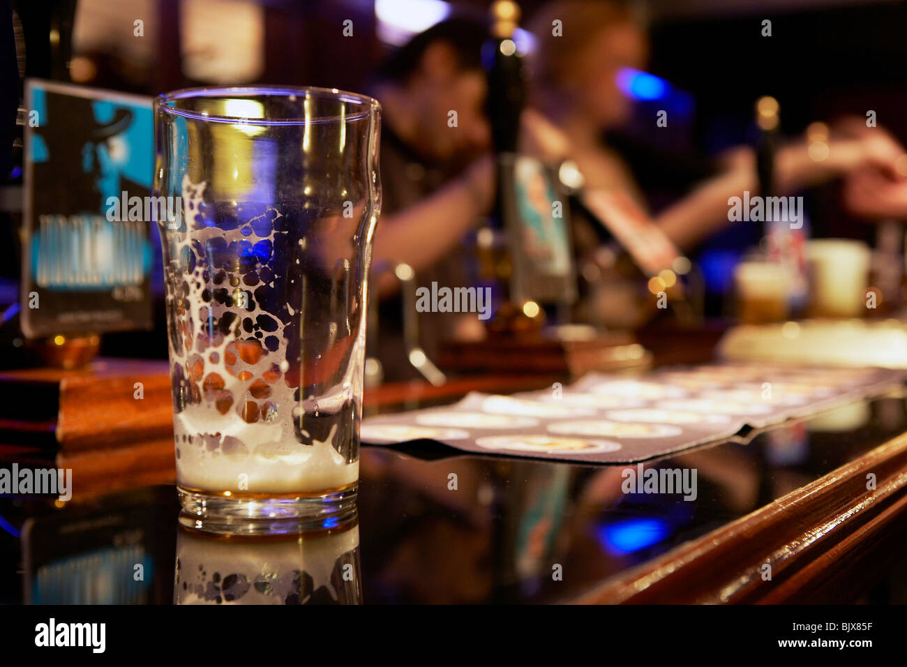 Empty pint glass on a bar - Stock Image