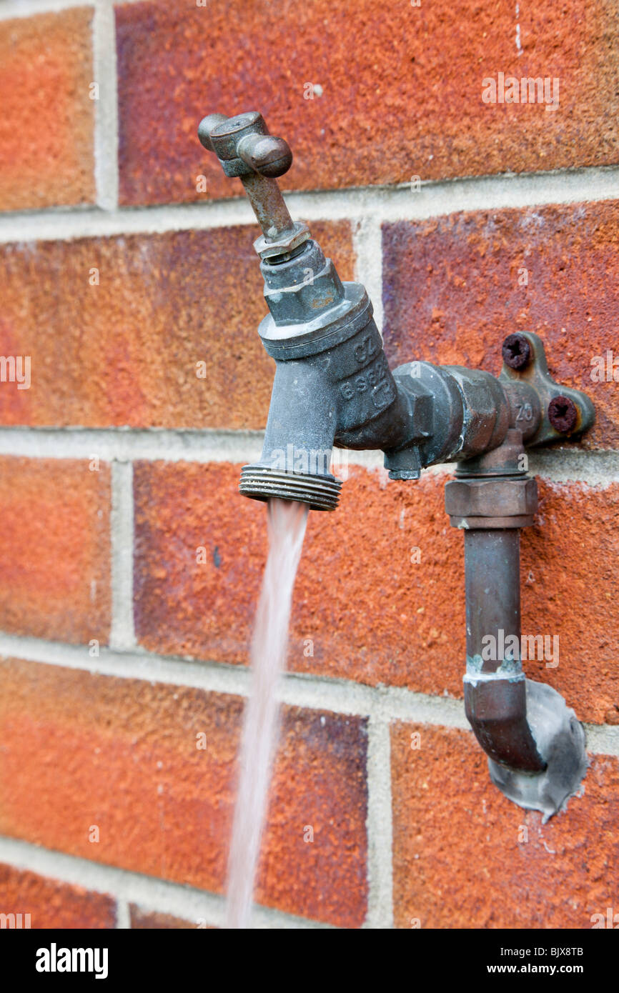 Running water flowing from an outside tap switched on and fixed to a brick wall - Stock Image