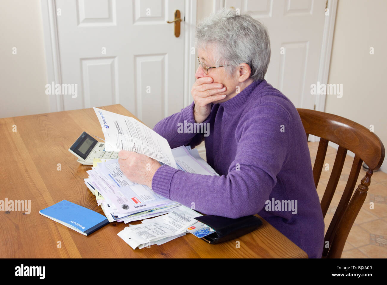 Worried senior woman pensioner with a big pile of bills with hand over her mouth looking shocked at a large credit - Stock Image