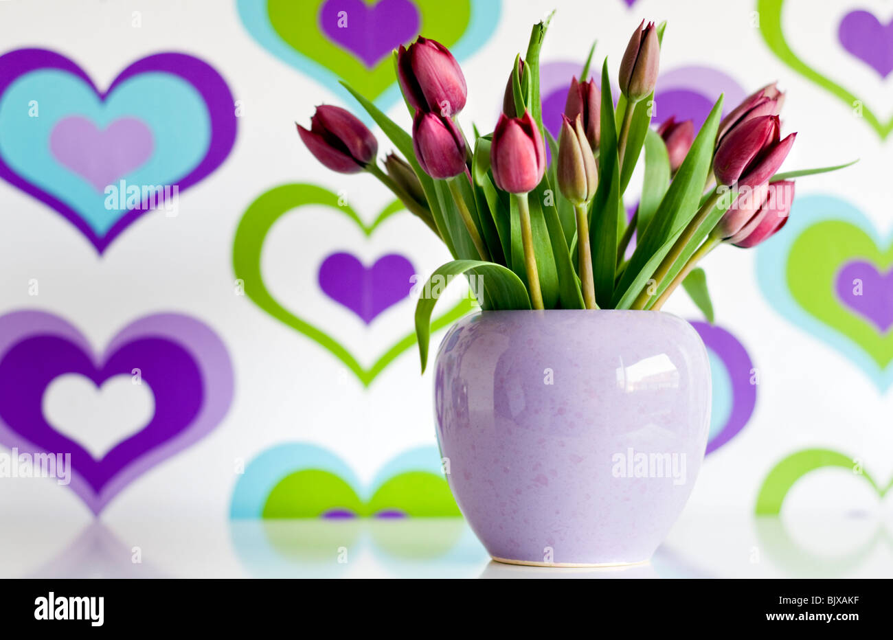 A vase of purple tulips in front of colorful wallpaper decorated with a heart pattern - Stock Image