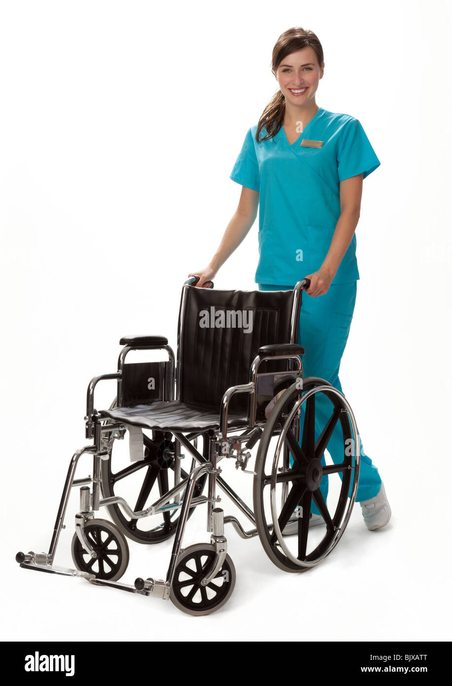 Studio photo of female health care worker standing beside wheelchair. White background. - Stock Image