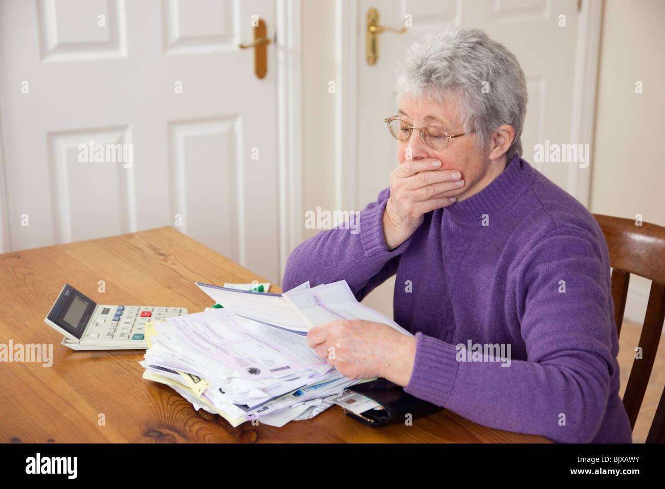 Senior woman pensioner with a big pile of bills on a table with hand over mouth looking shocked at large Council - Stock Image