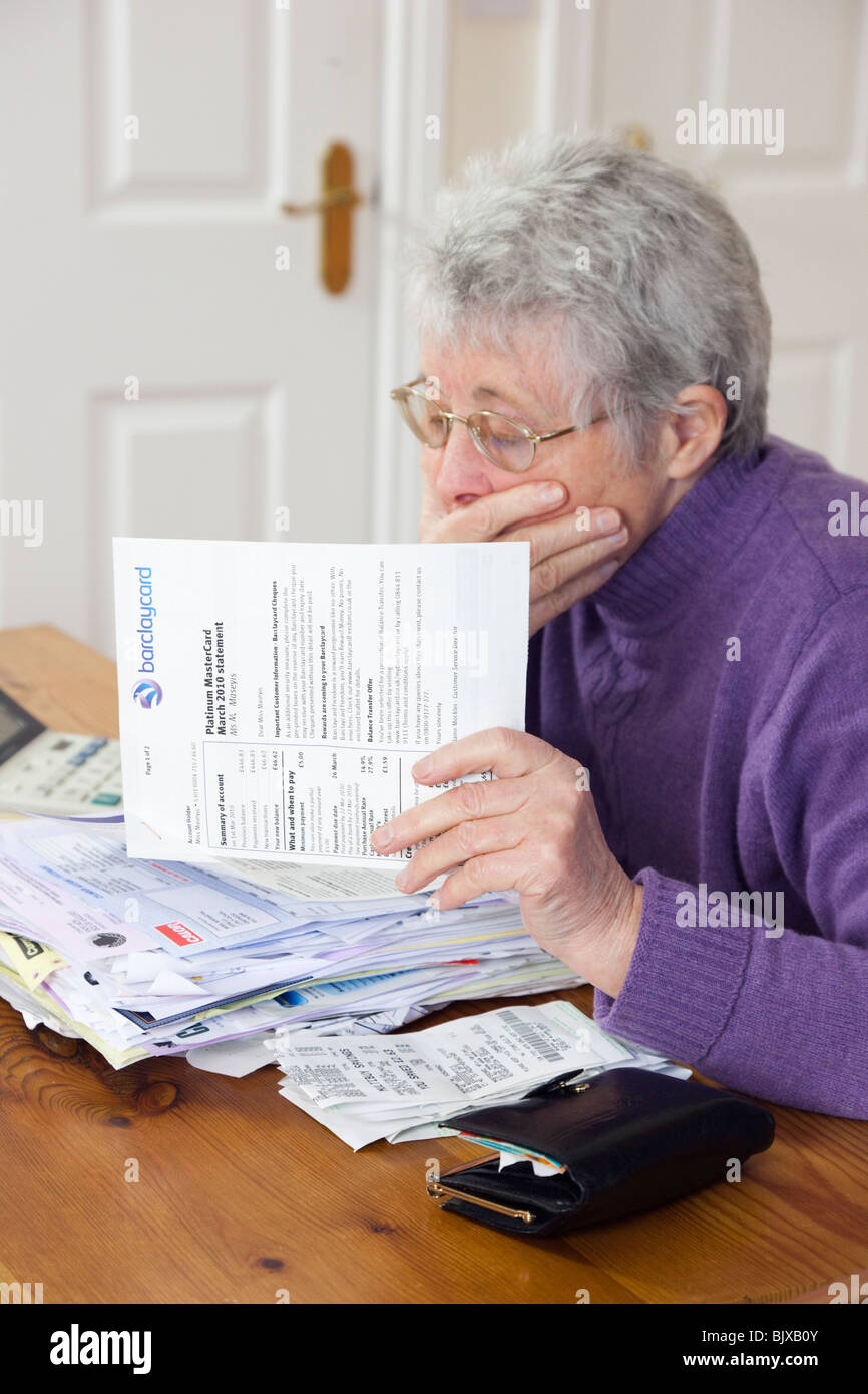 Shocked senior woman retiree pensioner with a big pile of bills with hand over her mouth looking worried at a large - Stock Image