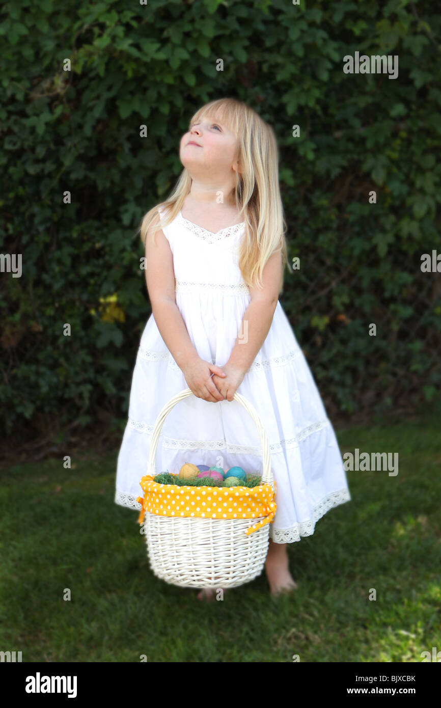 Sweet Little Girl Looking Up Holding Easter Basket with Eggs in a White Lace Dress - Stock Image