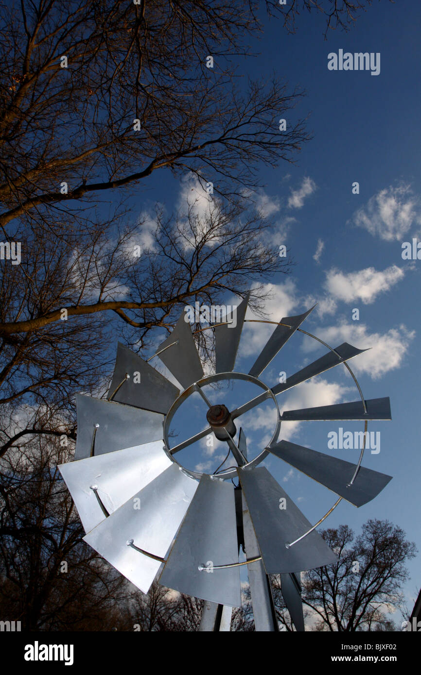 Decorative windmill with bare oak tree limbs and small clouds. - Stock Image