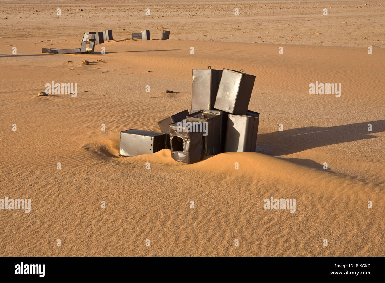 Fuel cans close to the abandoned Ford 30 CWT CMP truck from 1941/42 era sinking in the sand of the Western Desert, - Stock Image