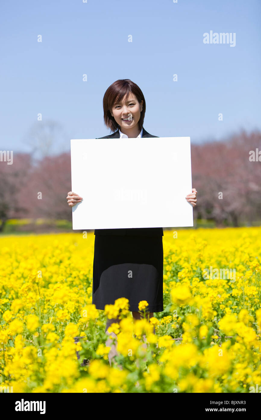 Young businesswoman holding blank placard - Stock Image
