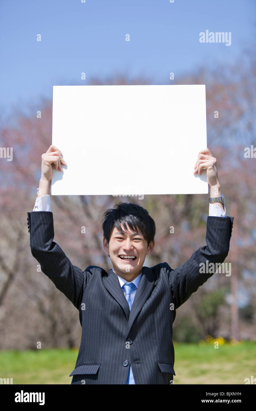 Young businessman holding blank placard - Stock Image