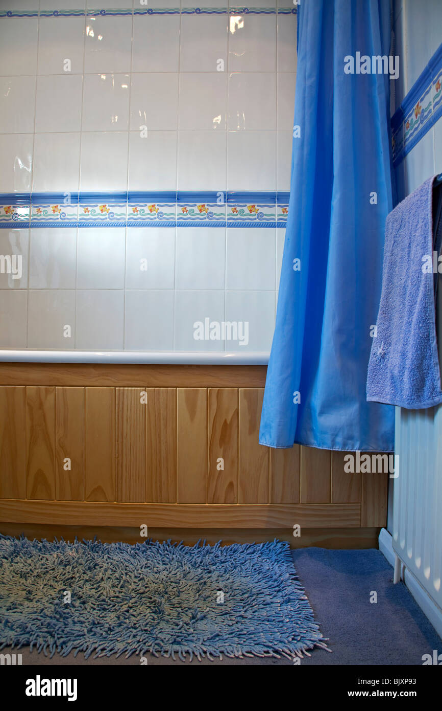 a bathroom with wooden paneling and white tiles Stock Photo ...