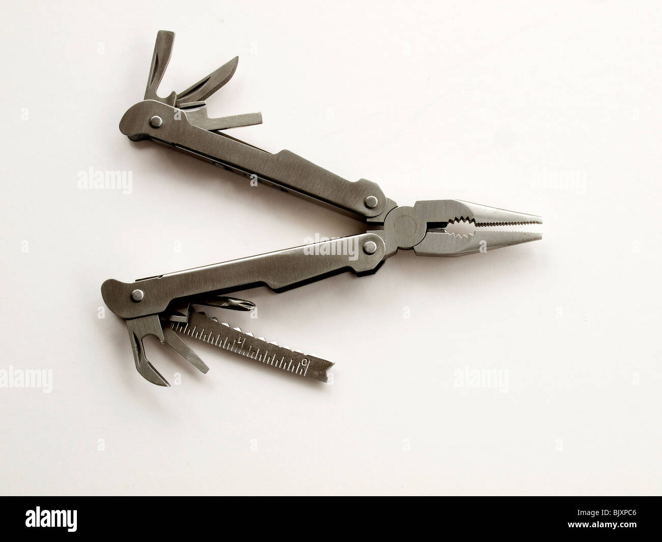 A multi--purpose hand tool on a white background - Stock Image