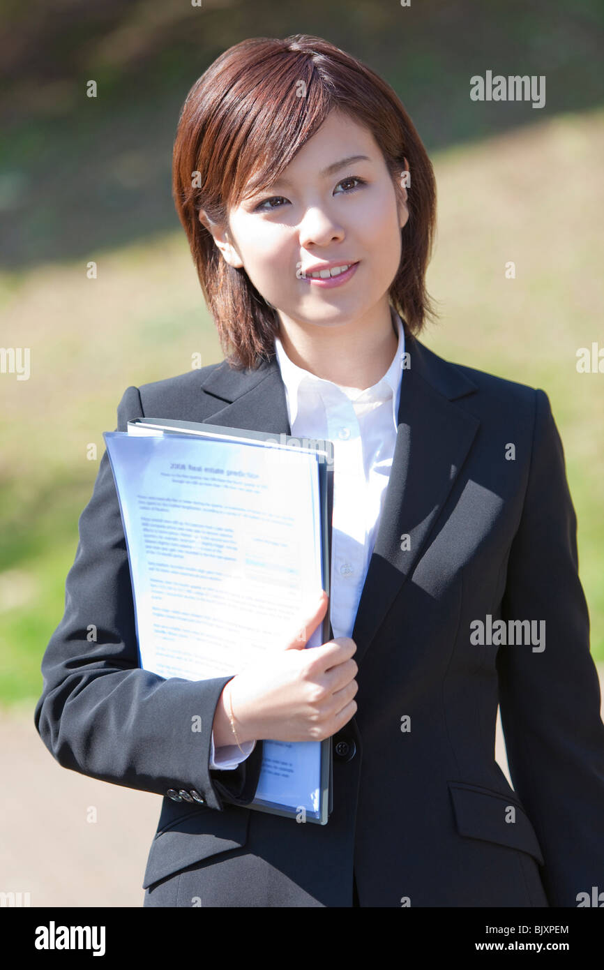 Young businesswoman holding documents - Stock Image