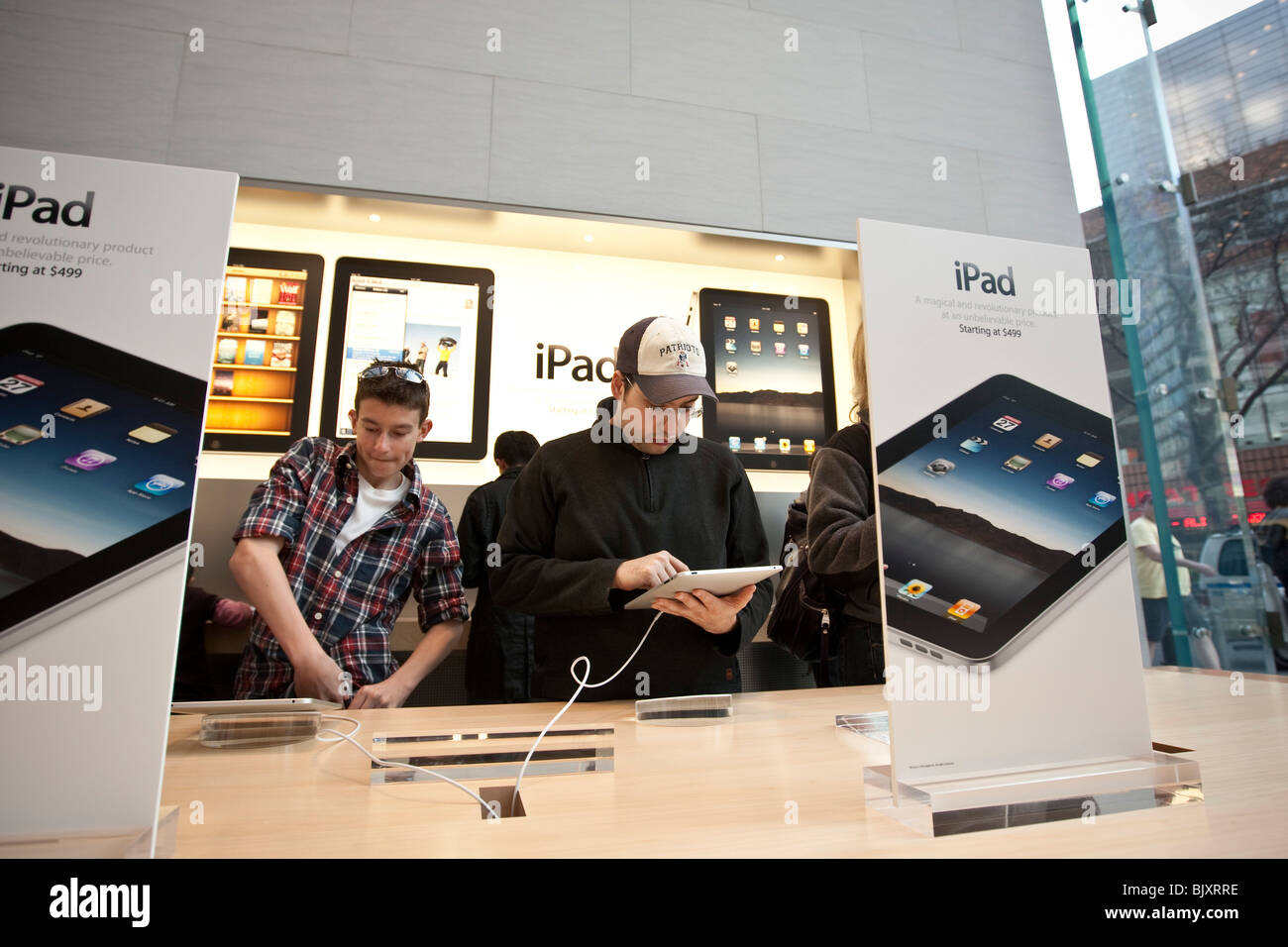 People try out the new iPad at the UWS Apple store in New York, USA, 3 April 2010. - Stock Image