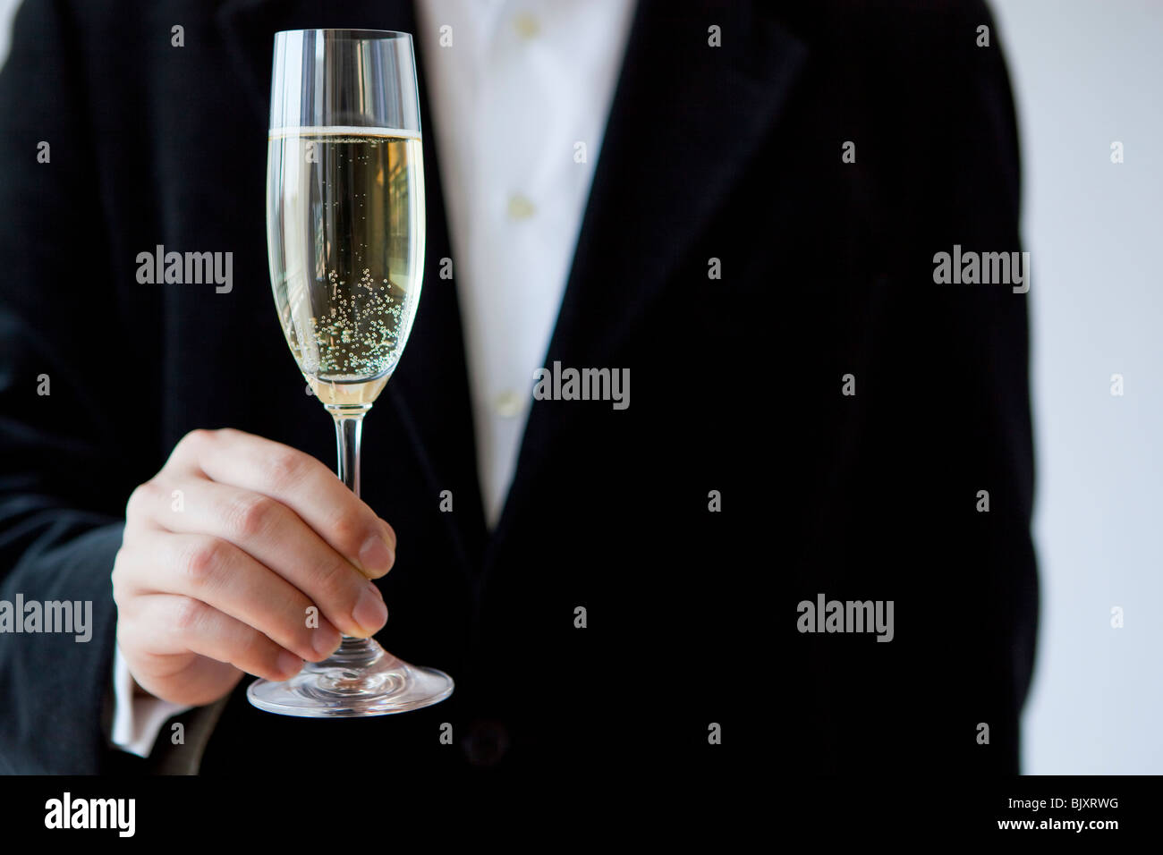 Young man holding champagne flute - Stock Image