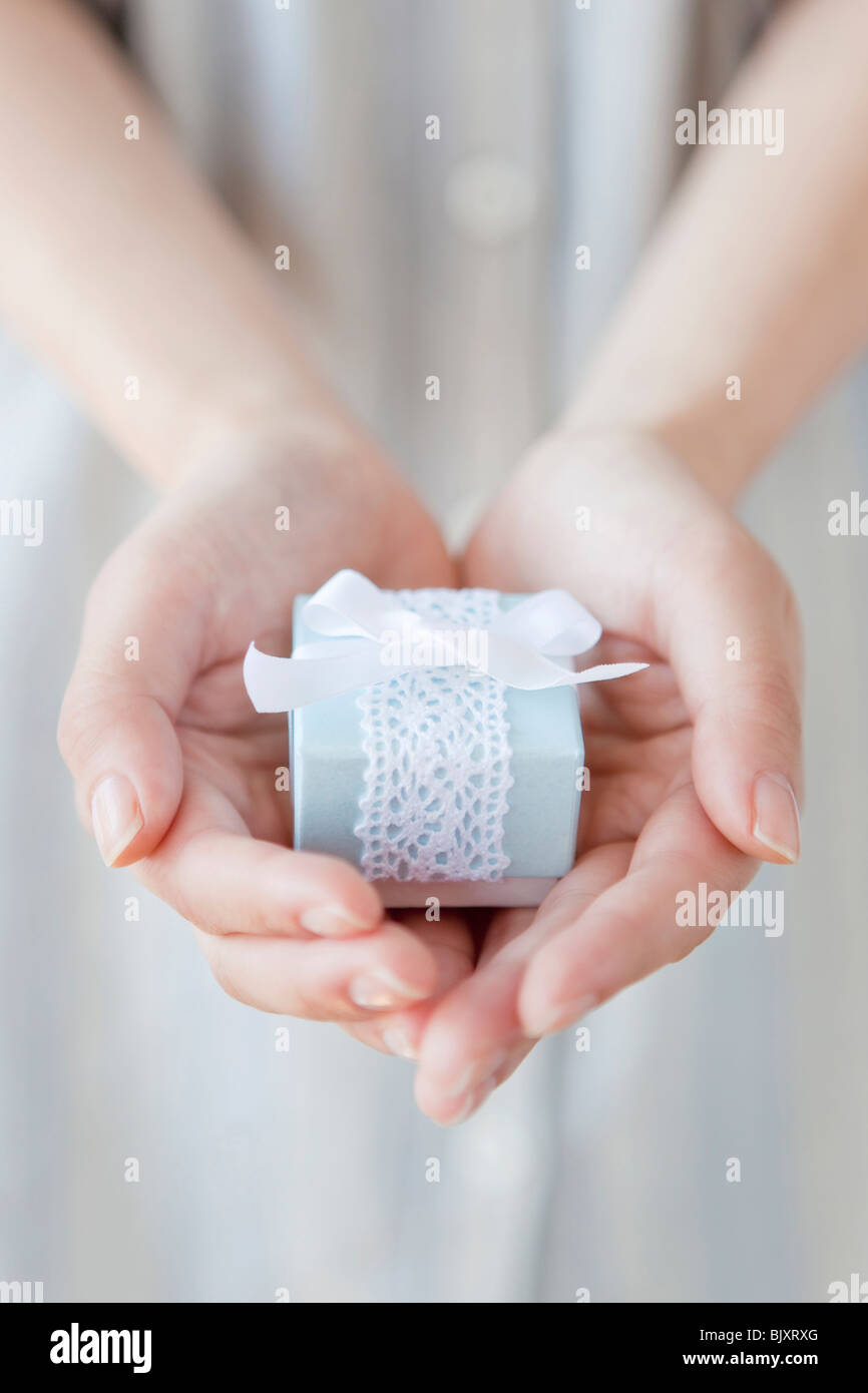 Young woman holding a present - Stock Image