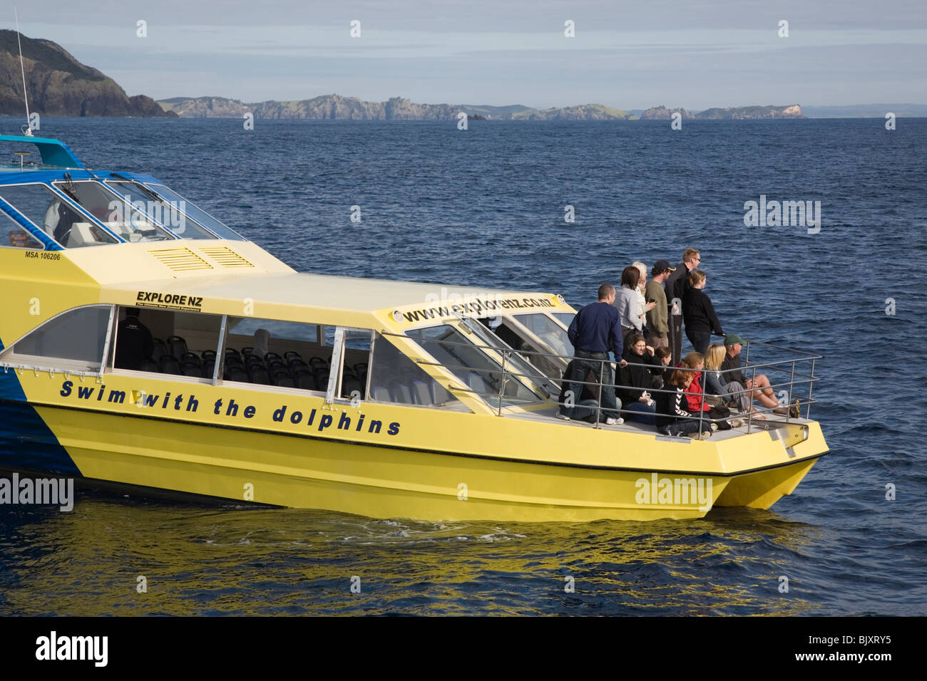 Bay of Islands North Island New Zealand. Dolphin watching tourist group on yellow 'Swim with the Dolphins' - Stock Image