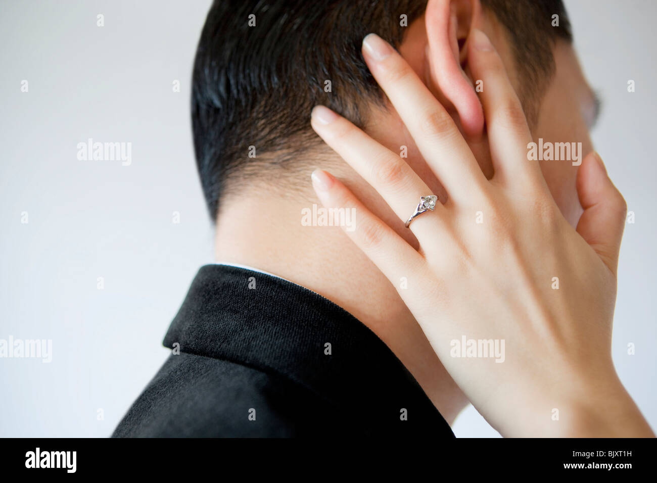 Hand of a young woman touching man's face - Stock Image