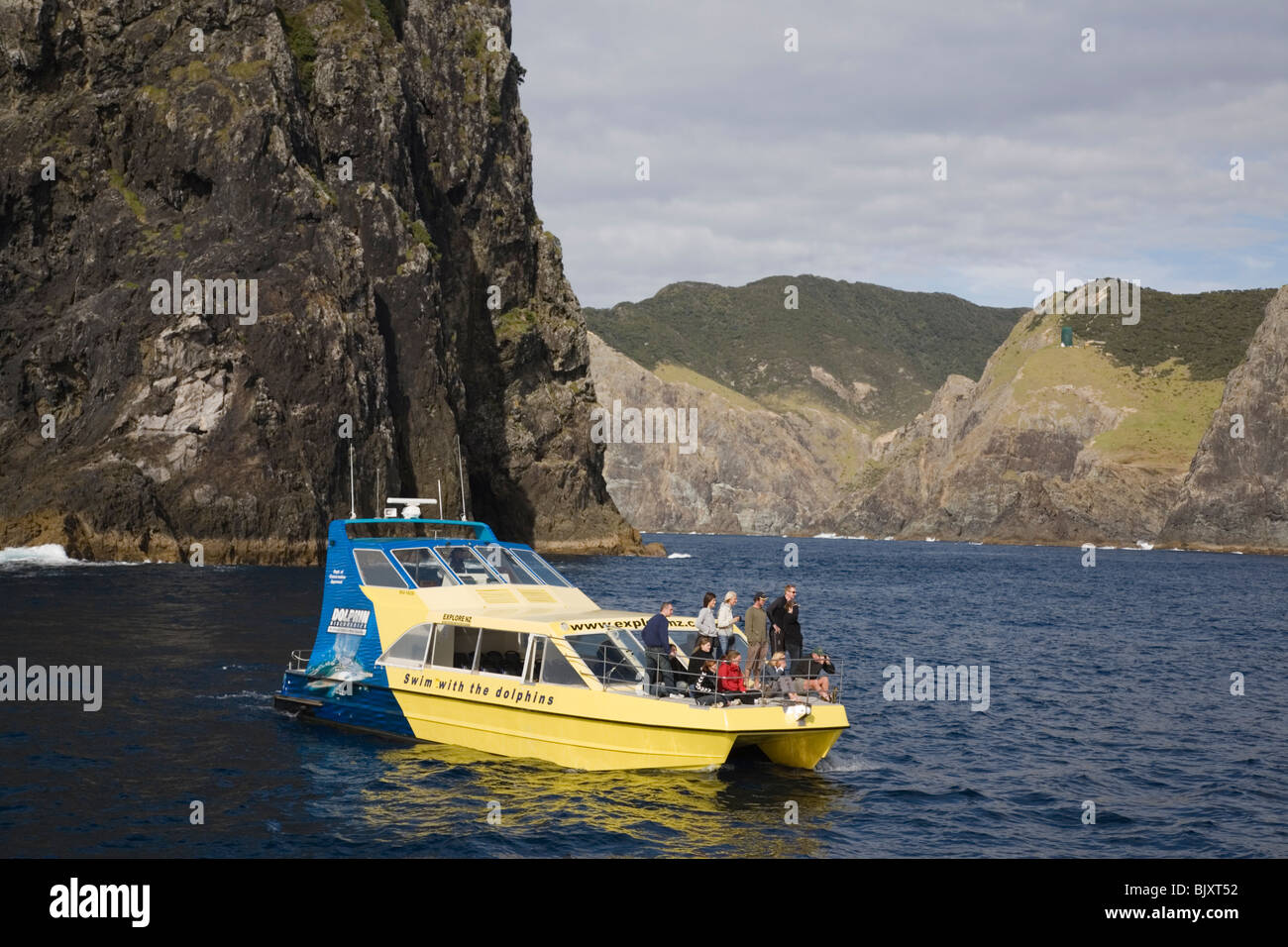 Bay of Islands North Island New Zealand. Dolphin watching tourist group by Piercy 'Hole in the Rock' island - Stock Image