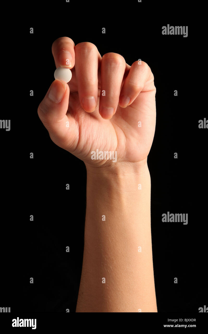 A female hand holding a small white pill between fingers - Stock Image