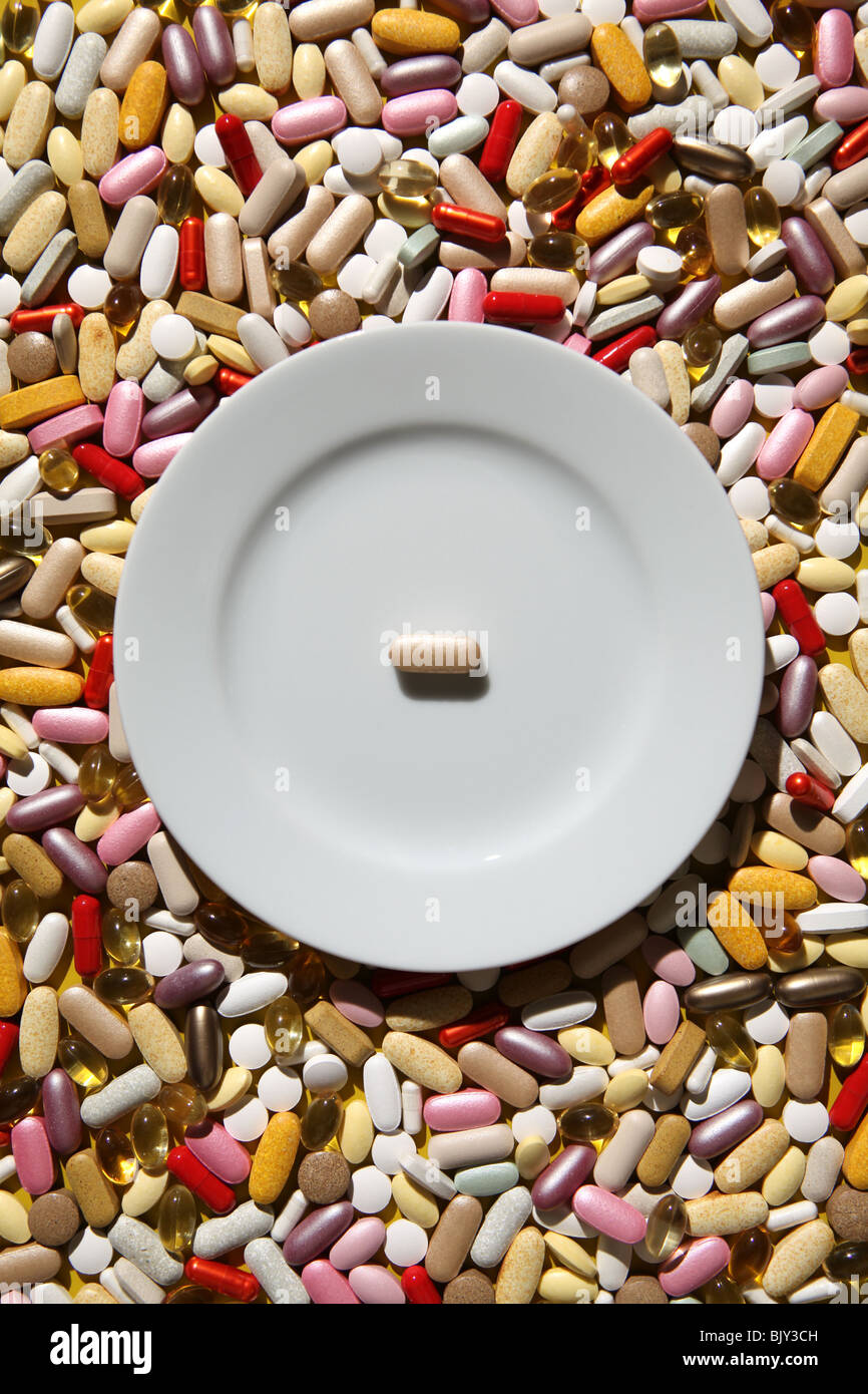 An empty white dinner plate with one pill on a background of colorful capsules, tablets and pills - Stock Image