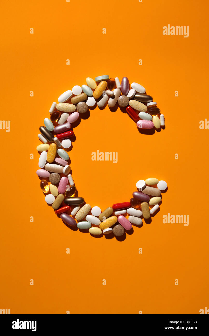 The shaped of the letter C formed with many colorful pills, tablets and capsules - Stock Image