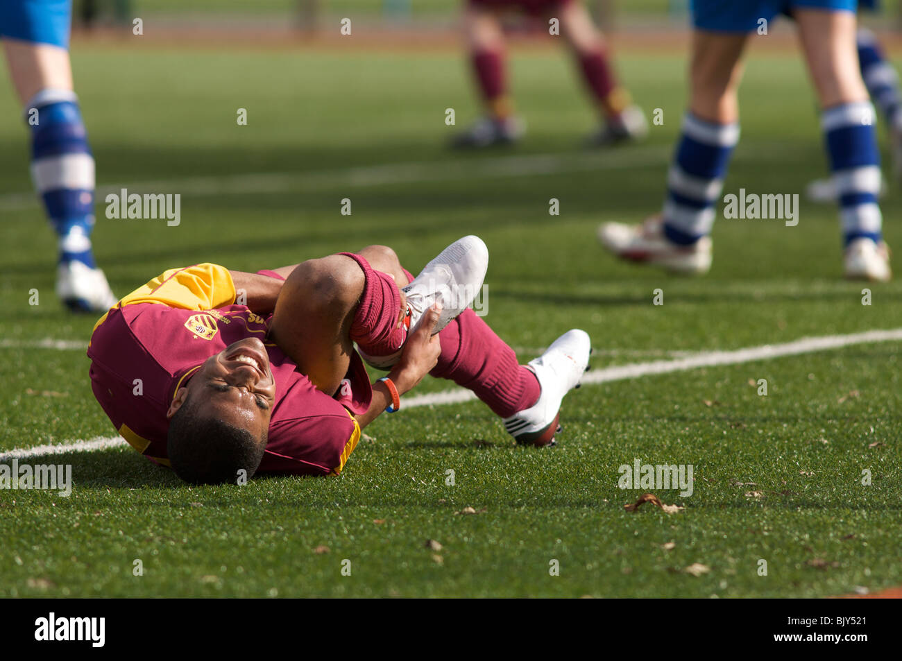 footballer writhes in agony after being injured - Stock Image