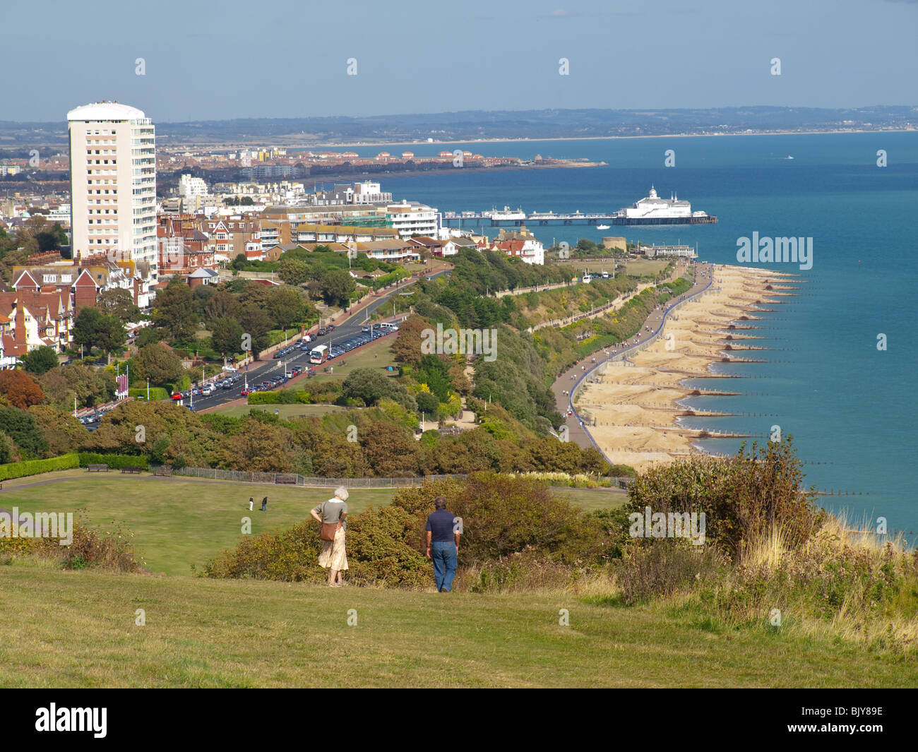 View of Eastbourne Seafront and Pier from South Downs Way with walkers in foreground , Sussex, England, UK Stock Photo
