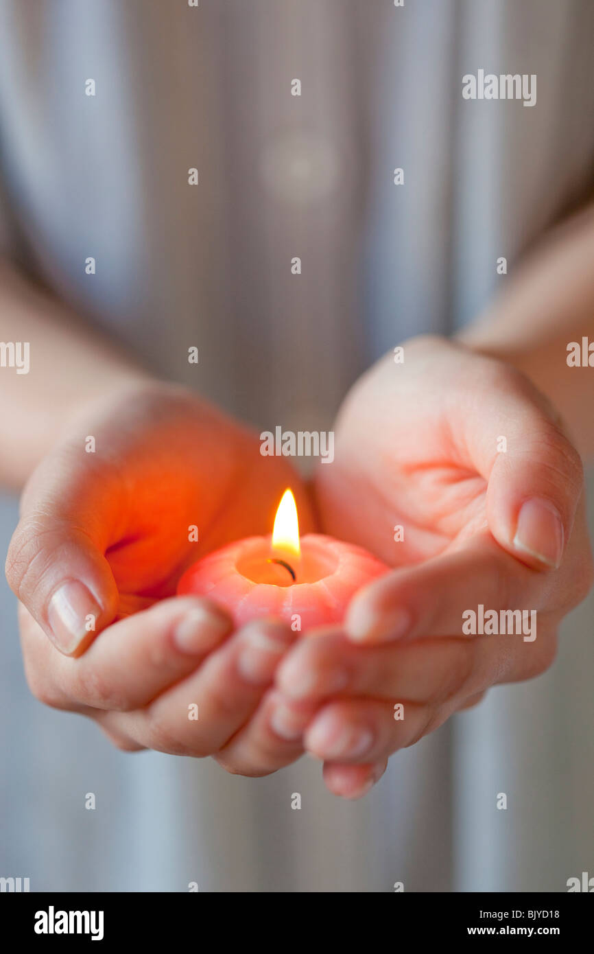 Hands of a woman holding candle - Stock Image