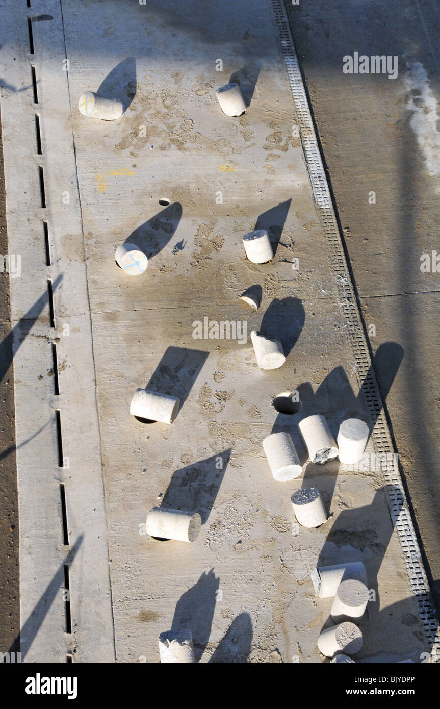 Concrete cores drilled out of new paving on motorway widening project for crash barrier supports - Stock Image