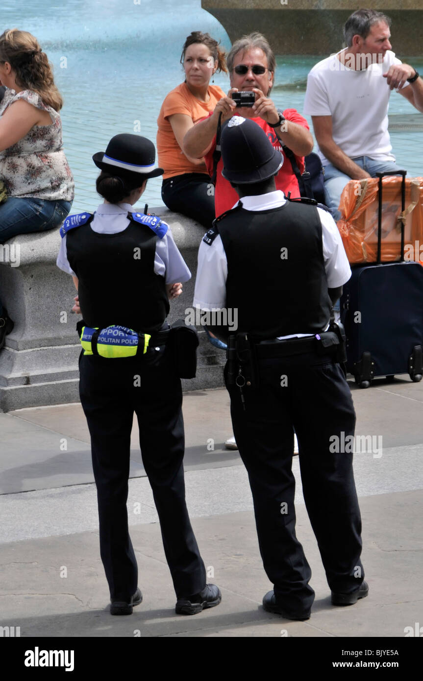 London  one PCSO and one police officer posing for tourist taking photo - Stock Image