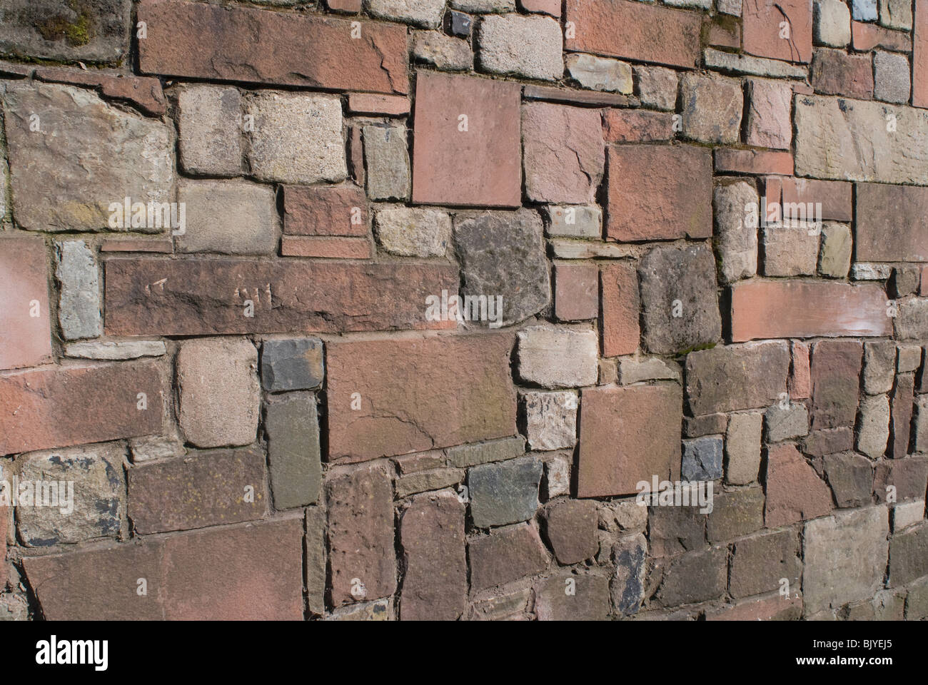 A solid stone wall made of sandstone limestone and granite. - Stock Image