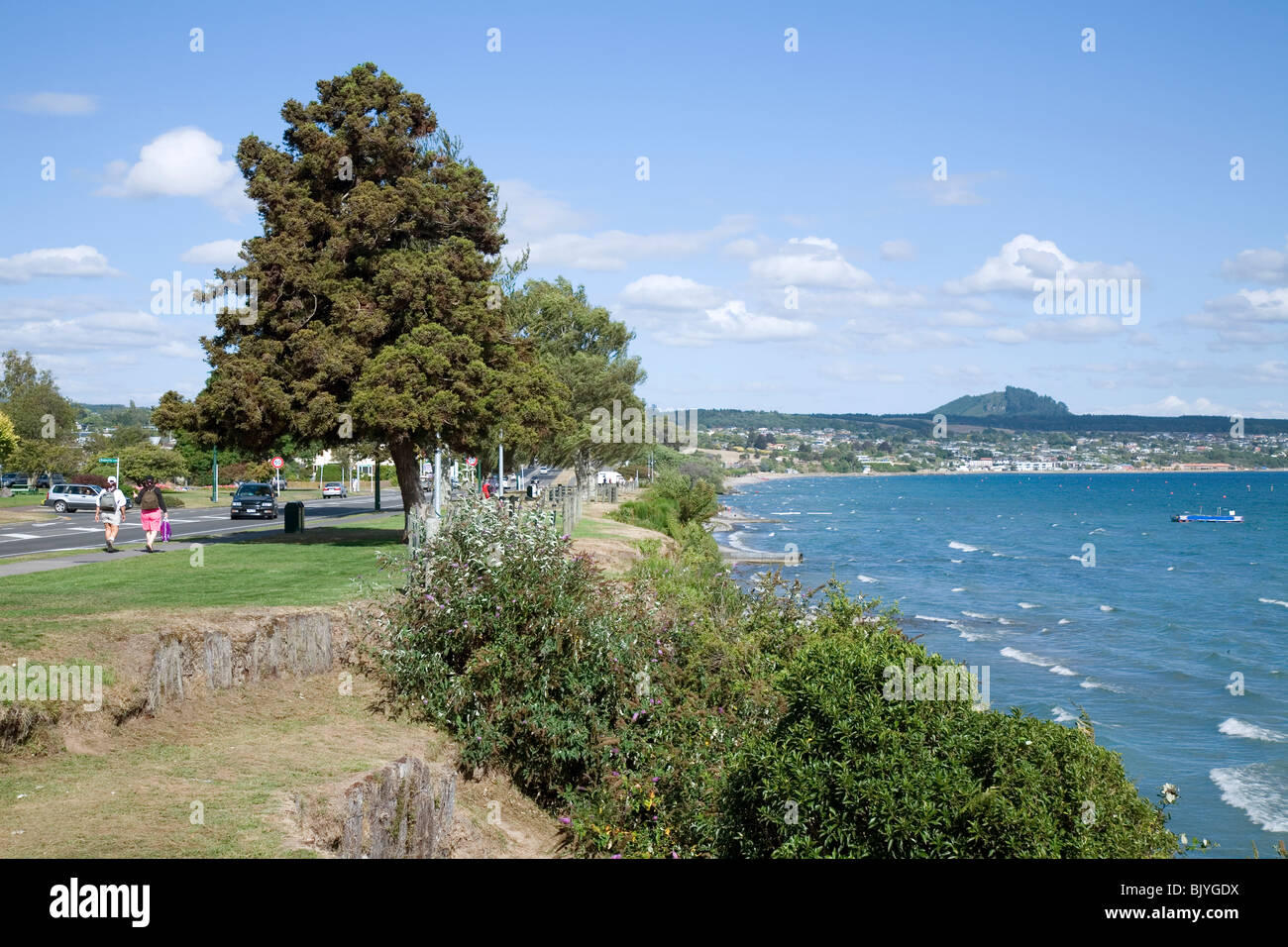 The neatly manicured and visitor friendly town of Taupo nestles on the shores of volcanically formed Lake Taupo - Stock Image