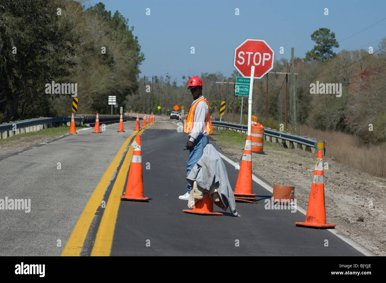 man working for highway road work crew tends the stop and caution sign in rural North Florida - Stock Image