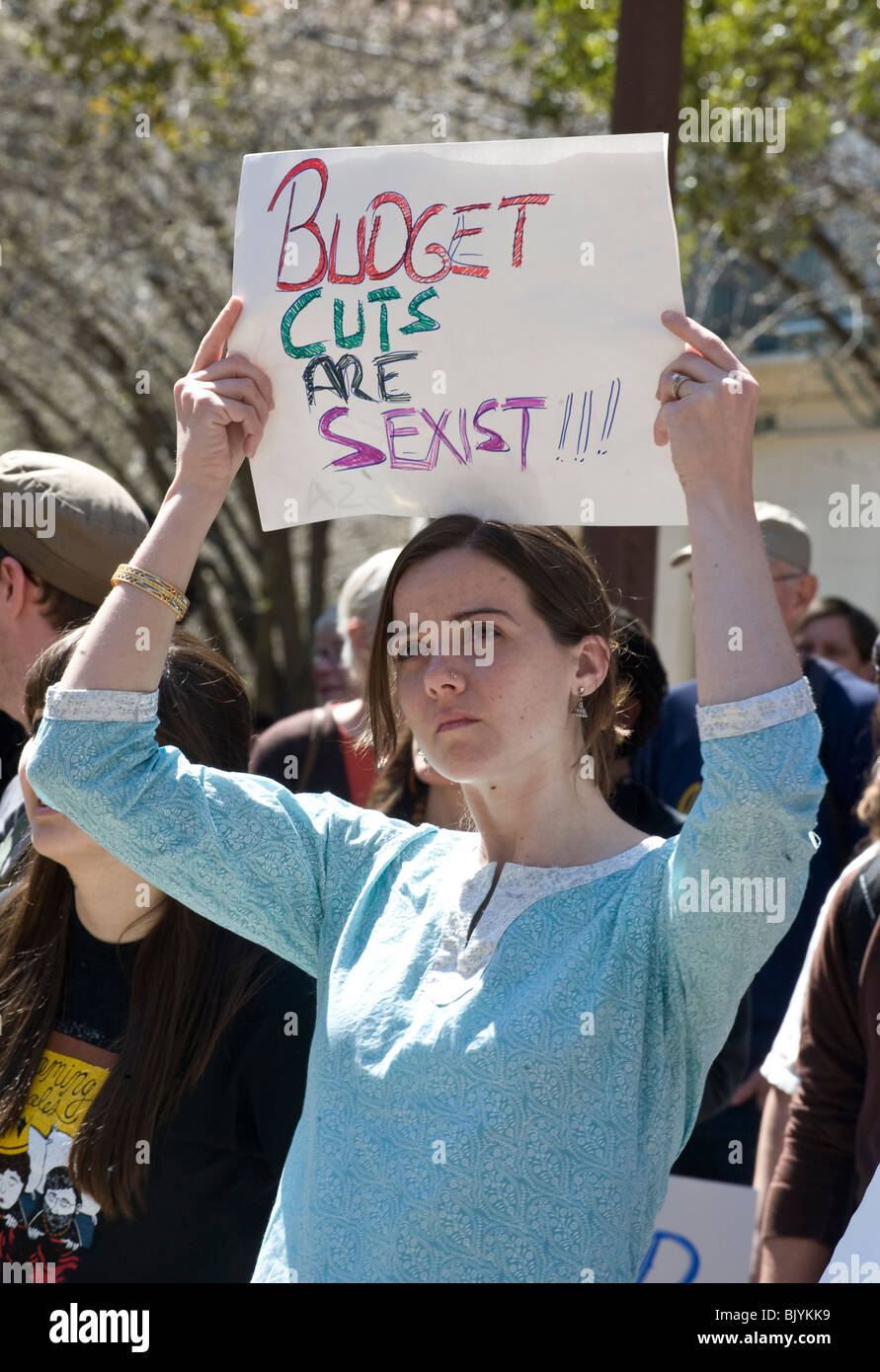 female college student holds sign saying budget cuts are sexist at