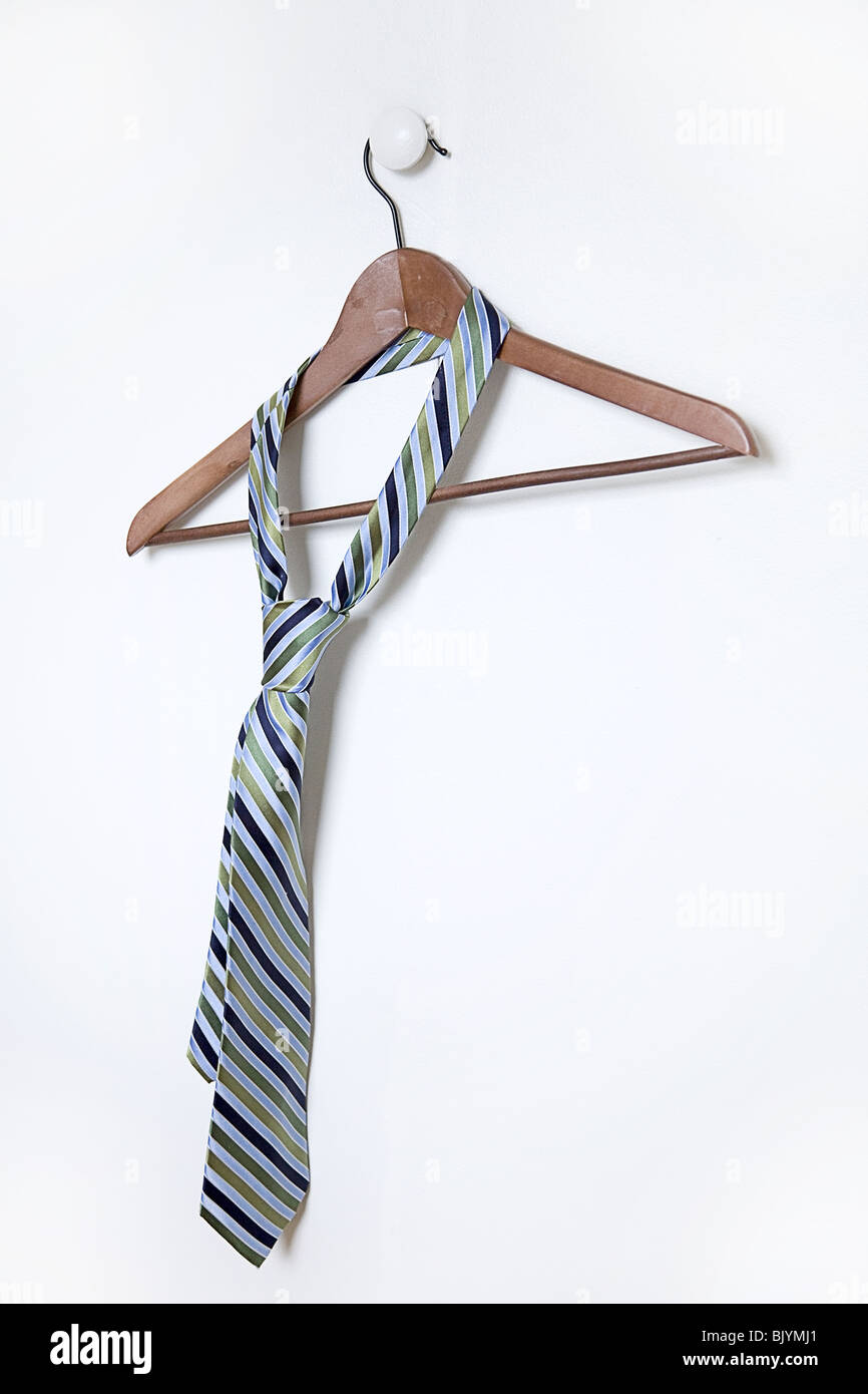 man's necktie hanging on a hanger on white handle - Stock Image