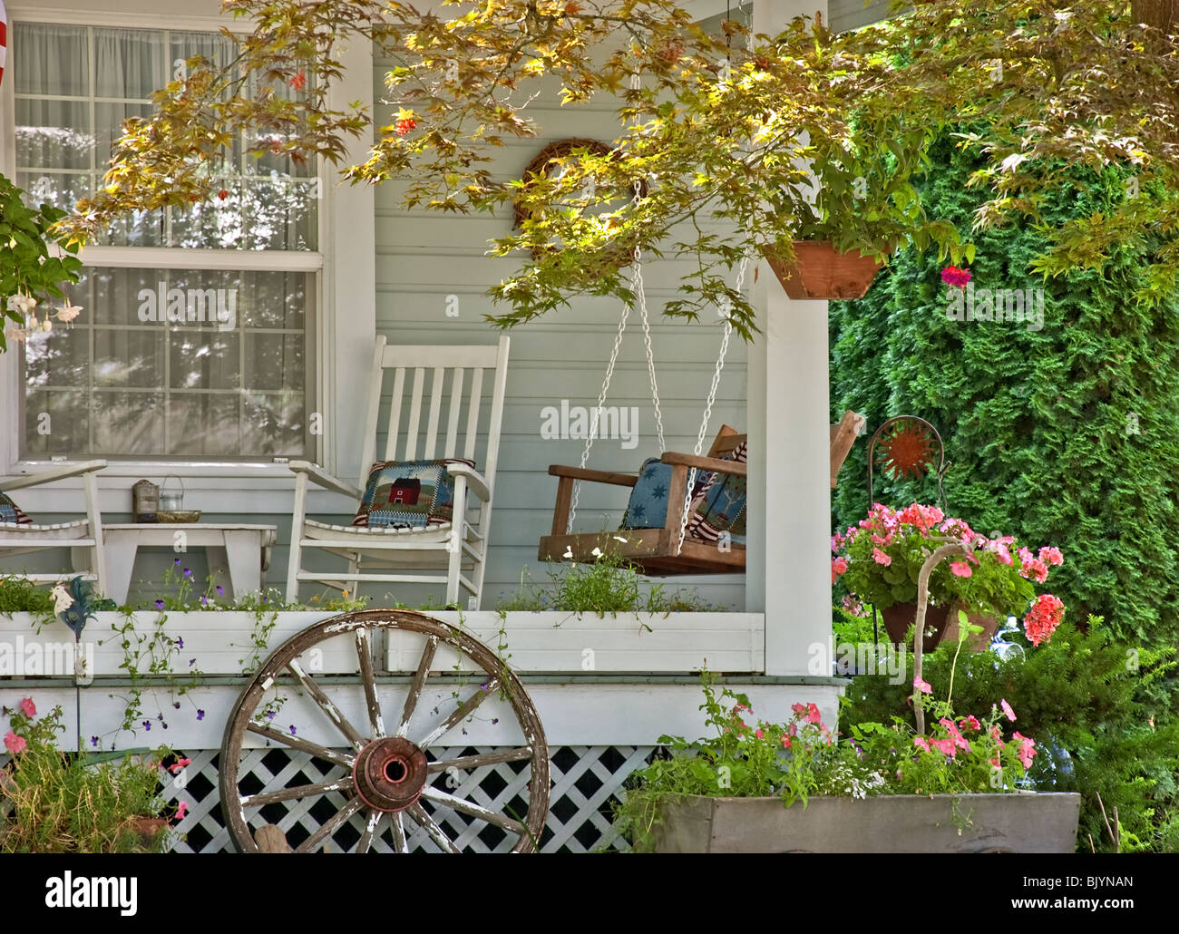 This cute welcoming scene is a detailed area of a home showing a summertime class porch scene with a swing, rocking - Stock Image
