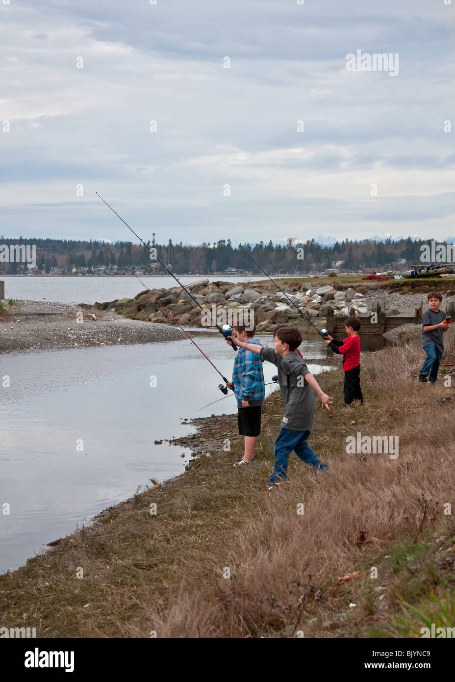 This 5 young boys are having a great time fishing on a cold spring day in Birch Bay Washington. Shot is full of - Stock Image